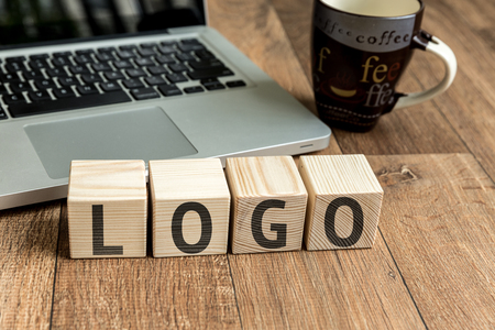 branded: Logo written on a wooden cube with laptop background