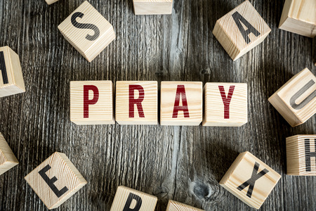 plea: Pray written on a wooden cube background Stock Photo