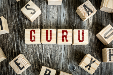 reputable: Guru written on a wooden cube background