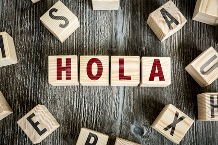 courteous: Hola (Hello in Spanish) written on a wooden cube background