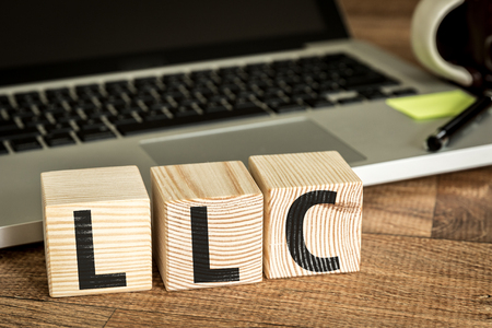 incorporation: LLC written on a wooden cube with laptop background
