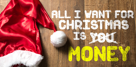 All I want for Christmas is money written on wooden background with santa hat Stock Photo