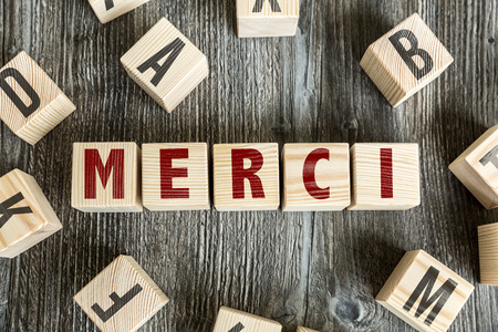 merci: Merci (Thank you in French) written on a wooden cube background Stock Photo