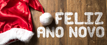 december 25: Feliz ano novo (Merry Christmas in Portuguese) written on wooden background with santa hat
