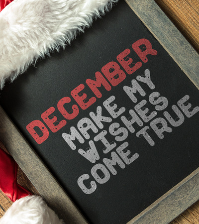 desires 25: December make my wishes come true written on blackboard with santa hat Stock Photo