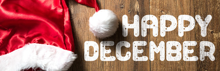 Happy December written on wooden background with santa hat
