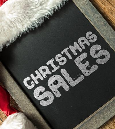 december 25th: Christmas sales written on blackboard with santa hat