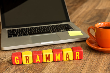 Grammar written on a wooden cube with laptop background Stock Photo