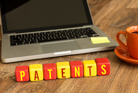 Patents written on a wooden cube with laptop background