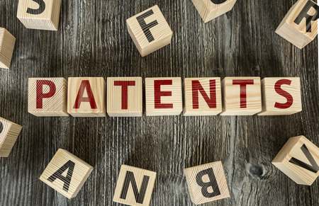 patents: Patents written on a wooden cube background