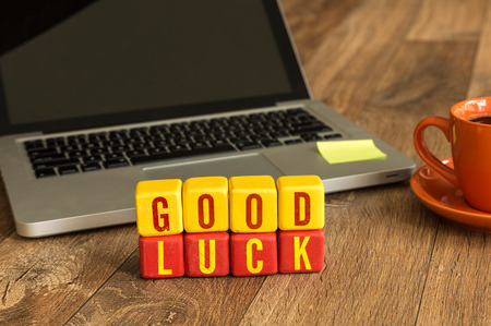Good luck written on a wooden cube with laptop background