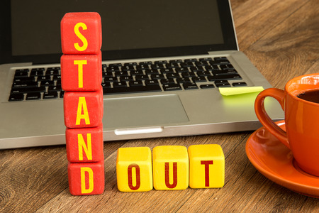 standout: Stand out written on a wooden cube with laptop background