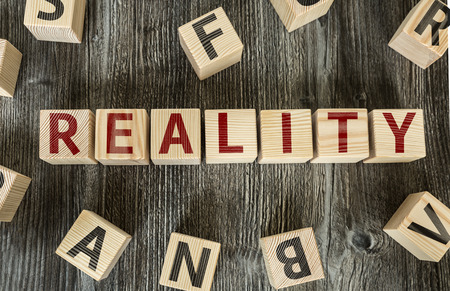 actuality: Reality written on a wooden cube background