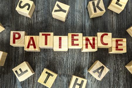 paciencia: La paciencia por escrito sobre un fondo cubo de madera Foto de archivo