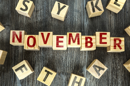 November written on a wooden cube background