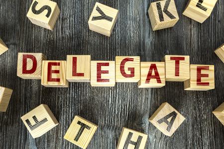 delegar: Delegar por escrito sobre un fondo cubo de madera Foto de archivo