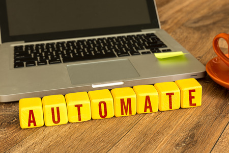 automate: Automate written on a wooden cube with laptop background