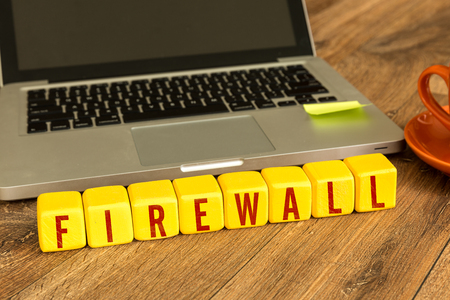 Firewall written on a wooden cube with laptop background