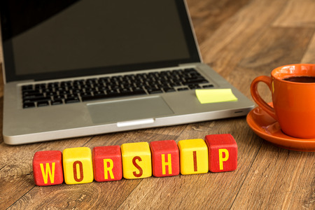 worshipper: Worship written on a wooden cube with laptop background