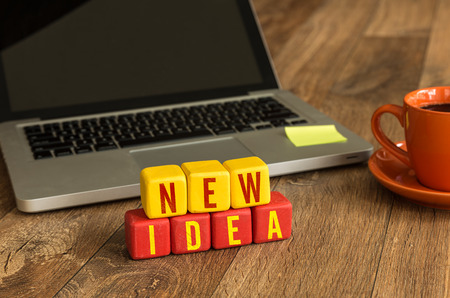 new idea: New idea written on a wooden cube with laptop background Stock Photo