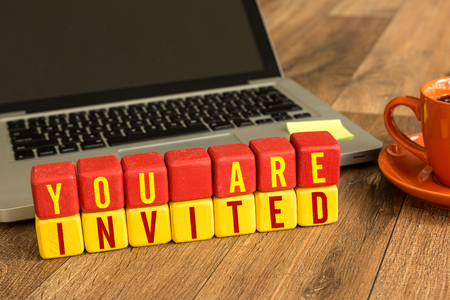 You are invited written on a wooden cube with laptop background
