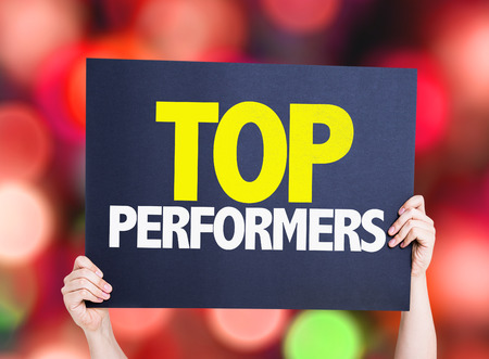 performers: Hands holding cardboard on bokeh background with text: Top performers Stock Photo