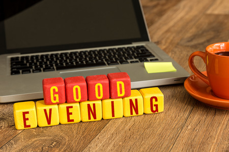 good evening: Good evening written on a wooden cube with laptop background Stock Photo