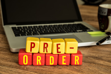 preorder: Pre-order written on a wooden cube with laptop background Stock Photo