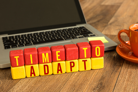 Time to adapt written on a wooden cube with laptop background