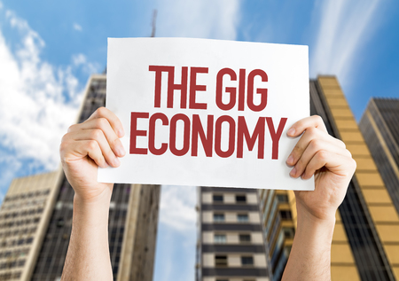 Hands holding cardboard on city background with text: The gig economy Stock Photo