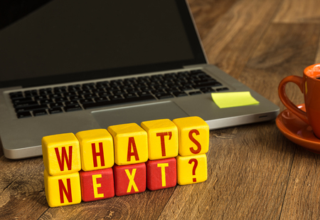 Whats next? written on a wooden cube with laptop background