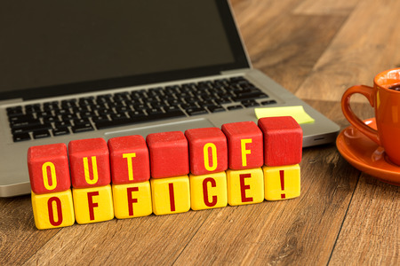 Out of office! written on a wooden cube with laptop background