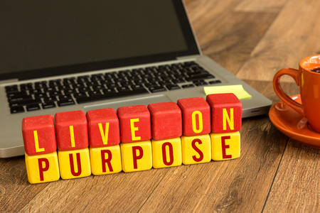 Live on purpose written on a wooden cube with laptop background