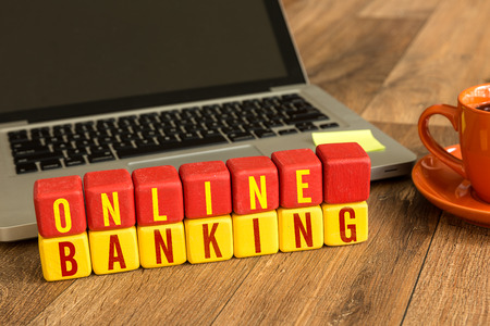 Online banking written on a wooden cube with laptop background Stock Photo