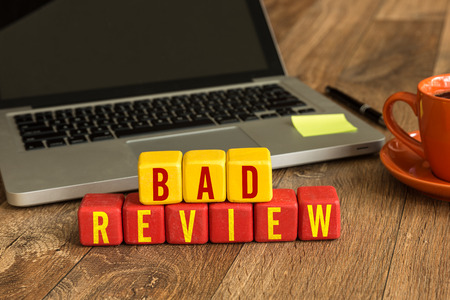 review: Bad review written on a wooden cube with laptop background