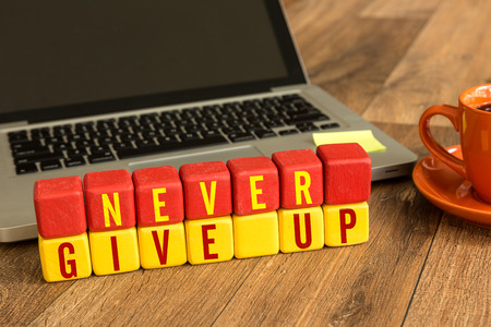 Never give up written on a wooden cube with laptop background