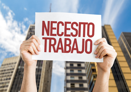 Hands holding cardboard on city background with text: Necesito trabajo (need a job in Spanish)