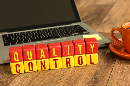 Quality control written on a wooden cube with laptop background