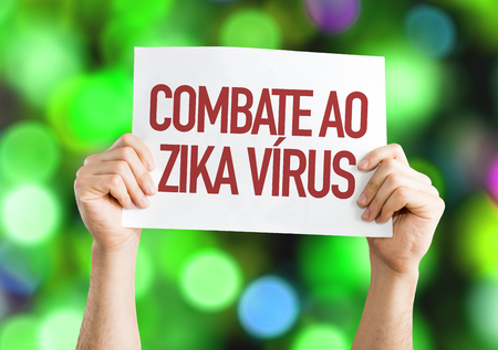 Hands holding cardboard on bokeh background with text: Combate ao zika virus (against zika virus in Portuguese)