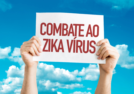 Hands holding cardboard on sky background with text: Combate ao zika virus (against zika virus in Portuguese)