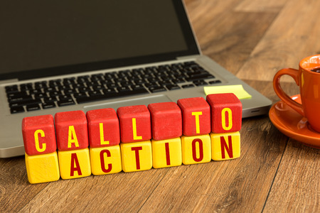 Call to action written on a wooden cube with laptop background
