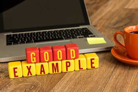 Good example written on a wooden cube with laptop background