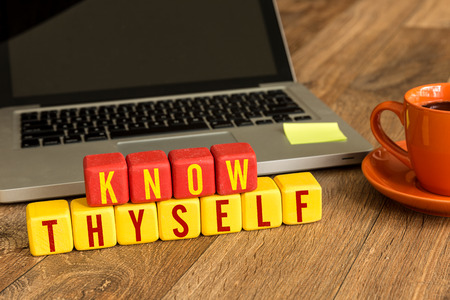 Know thyself written on a wooden cube with laptop background