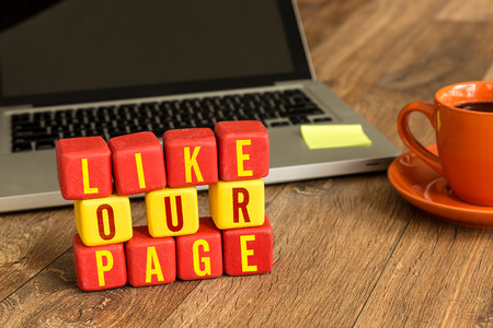 Like our page written on a wooden cube with laptop background Banque d'images