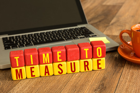 verify: Time to measure written on a wooden cube with laptop background