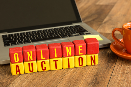 Online auction written on a wooden cube with laptop background Stockfoto