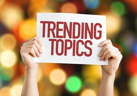 topics: Hands holding cardboard on bokeh background with text: Trending topics