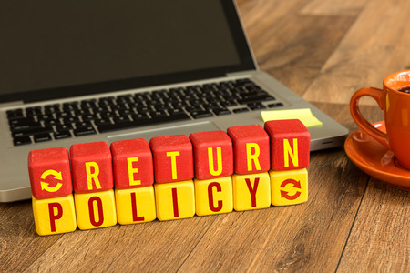 Return policy written on a wooden cube with laptop background Archivio Fotografico