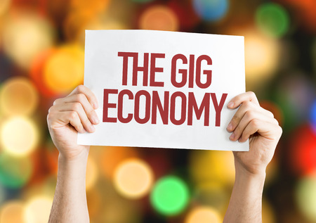Hands holding cardboard on bokeh background with text: The gig economy Standard-Bild