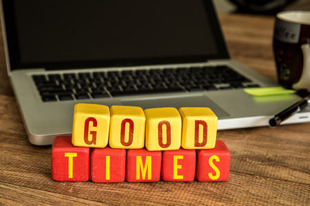 good times: Good times written on a wooden cube with laptop background